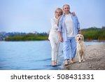 Stock photo senior couple and big dog on riverside 508431331