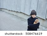 Small photo of little homeless boy holding a teddy bear, specifically biased composition, poverty, city, street