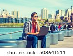Small photo of East Indian American student travels, studies in New York, wearing red v neck T shirt, gray hooded sweatshirt, sunglasses, sits by river, works on laptop computer, thinks. Brooklyn on background.