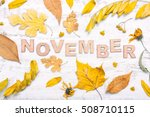 """Small photo of The word """"november"""" with yellow leaves on a white wooden background. Autumn composition"""
