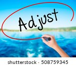 Small photo of Woman Hand Writing Adjust on blank transparent board with a marker isolated over water background. Business concept. Stock Photo