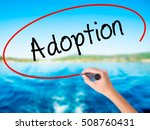 Small photo of Woman Hand Writing Adoption on blank transparent board with a marker isolated over water background. Business concept. Stock Photo