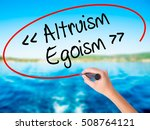 Small photo of Woman Hand Writing Altruism - Egoism on blank transparent board with a marker isolated over water background. Business concept. Stock Photo