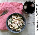 Small photo of Pasta penne is cooked al dente, then mixed with sliced ham, feta cheese and basil. Dressing is made with olive oil, bit of vinegar, salt and pepper. Served with glass of soda on white rustic table.