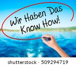 Small photo of Woman Hand Writing Wir Haben Das Know How! (We Have the Know-How in German) on blank transparent board with a marker isolated over water background. Business concept. Stock Photo