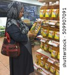 Small photo of Labuan,Malaysia-Nov 4,2016:Housewife consumer shopping cooking oil at supermarket.Wef Nov 1,2016,all bottled cooking oil based on market price but subsidy continue & limited to packed in 1kg polybags.