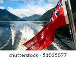 Flag of New Zealand against plenty stern wave of cruise ship at Doubtful Sound - stock photo