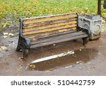 Small photo of A wooden bench stands against the wall all wet from the rain.