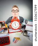 Small photo of Paper work against time. Young expressive woman in office with big red clock. Unhappy businesswoman so far to ending her work.