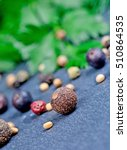 Small photo of Juniper,allspice mustard seeds and parsley on slate closeup