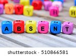 Small photo of The colorful word Absent on wooden table