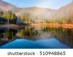 view on crystal clear lake with smoke and reflection on the water near the spruce forest in fog at the foot of the mountain at sunrise - stock photo