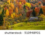 woodshed behind the fence on the hillside cowered with foliage near forest in autumn mountains - stock photo