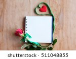 notebook with rose on wooden... | Shutterstock . vector #511048855