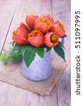 Small photo of Orange abutilon flowers and leaves in tin jug.