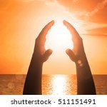 hands holding the sun at dawn | Shutterstock . vector #511151491