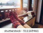 feet in woollen socks by the... | Shutterstock . vector #511169461