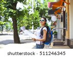 Small photo of Cheerful woman searching direction on location map while traveling abroad in summer, happy female tourist searching road to hotel on atlas in a foreign city during vacation