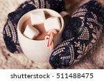 hands in cozy mittens holding... | Shutterstock . vector #511488475