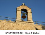 Detail of bell and cross against blue sky. - stock photo