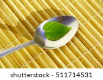 Small photo of Alternative treatment. Metal spoon with a green heart shape leaf on a bamboo mat.