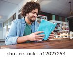 man reading a book in cafeteria | Shutterstock . vector #512029294