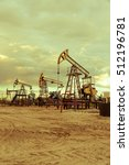 Small photo of Oil pump jacks group and wellhead with valve armature during sunset on the oilfield. Oil and gas concept. Dramatic cloudy sky background. Toned.