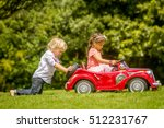 Stock photo young happy children boy and girl driving a toy car outdoors in park 512231767