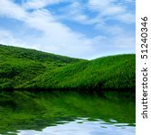 Summer landscape scenery background. Water, green grass and blue sky. - stock photo