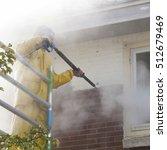 man in yellow rain suit cleans... | Shutterstock . vector #512679469