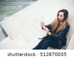 Small photo of Beautiful smiley young woman with nice make-up is sitting on the concrete steps and doing live snap-chat vlog video on her smart-phone. Copy-space area for your text or advertisement text
