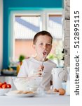 Small photo of Child tasting pastry from mixer agitator . Boy helping in the kitchen. Baking with children