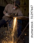 Stock photo a man in a shop cutting metal with his torch 51297667