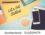 Small photo of Notepad on workplace table and written LET'S GET STARTED concept