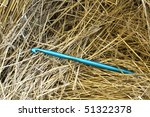 A conceptual image of a large crocheting needle in a haystack. - stock photo