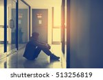 Small photo of Silhouette of businessman sitting alone,Sad and Serious Man sitting hug his knee alone t of closeing office.With his reflecing shodow.Dramatic moment.Split tone instragram like.With hot light process.