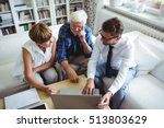 Small photo of Senior couple planning their investments with financial advisor in living room