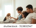 Stock photo happy family playing with their dog in bed 513832567