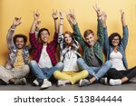 Small photo of Multiethnic group of smiling young people celebrating success and showing peace sign with raised hands over yellow background