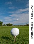 golf ball on tee with fair skies overhead - stock photo