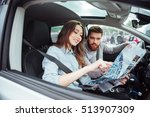 Couple In Car With Map. Man At...