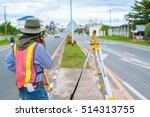 A Surveyor At Work With An...