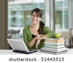 young woman posing as a student or teacher with books, laptop, and apple, wearing glasses and green top - stock photo