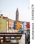 Small photo of Burano, Italy - March 18, 2012: A belfry rises behind colorful buildings on the Island of Burano,Italy while unused boats are tied alongside a canal.