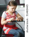 Small photo of Little girl reading book aloud at cafe table