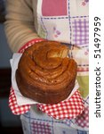 """Small photo of View of a woman's hand holding a traditional portuguese """"folar"""" cake."""