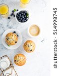 Small photo of Bright and airy breakfast with blueberry muffin, big cup of coffee and milk in bottles overhead view with copyspace