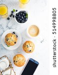 Small photo of Bright and airy breakfast with blueberry muffin, big cup of coffee and smartphone overhead view with copyspace