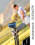 Golf clubs with a blurry female player on the background - stock photo