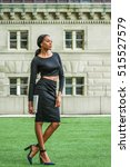 Small photo of African American Business Woman Fashion in New York. Lady wearing black long sleeve crop top, skit, high heel pumps shoes, holding laptop computer, stands on green lawn outside office building.